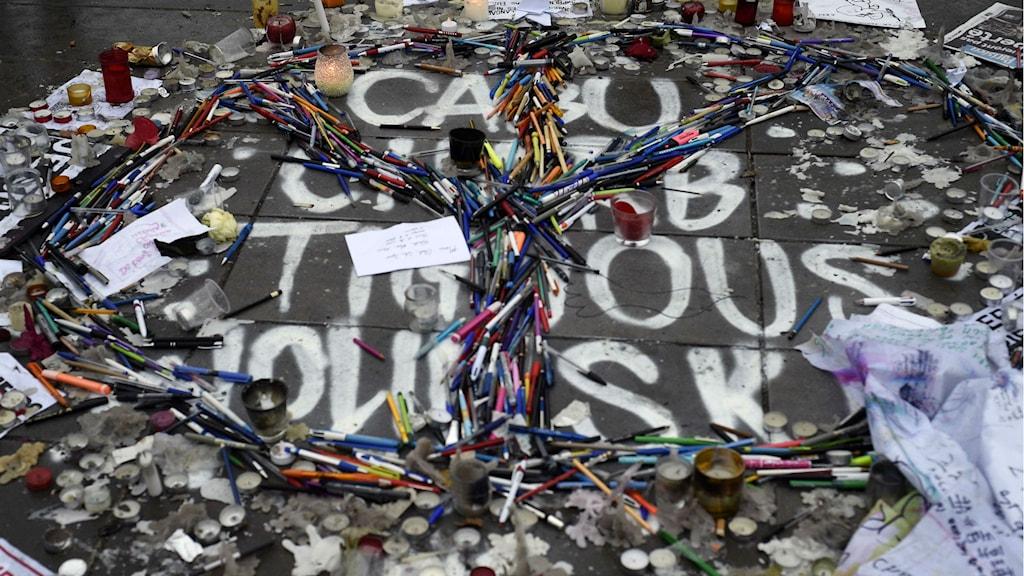 Pennor på marken bildar formen av ett fredstecken, för att hedra de mördade satirtecknarna på Charlie Hebdo. Foto: Martin Bureau Afp/TT