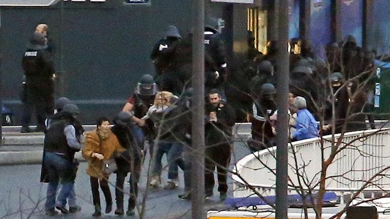Gisslan leds ut från kosheraffären i Paris efter att gisslandramat klarats upp av polisen. Foto: TT.