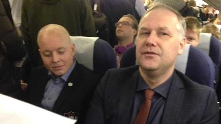 Björn Söder (SD) bredvid Jonas Sjöstedt (V) på flygplanet på väg mot Folk och försvar. Foto: Tomas Ramberg / Sveriges Radio