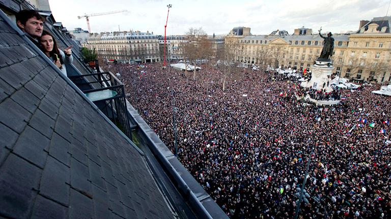 Boende vid Place de la Republique tittar ut över ett hav av människor i Paris. Foto: TT