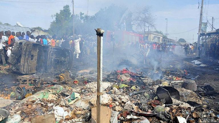 Människor samlas på en plats vid en marknad i Maiduguri där en bilbomb exploderat. Foto: Jossy Ola/TT.