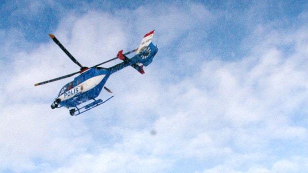 Polishelikopter flyger under snnöfall. Foto: TT