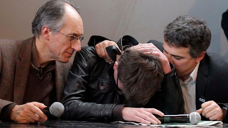 Nye chefredaktören för den franska satirtidningen Charlie Hebdo, Gerard Biard och krönikören Patrick Pelloux tröstar tecknaren Luz. Foto: Christophe Ena/TT.
