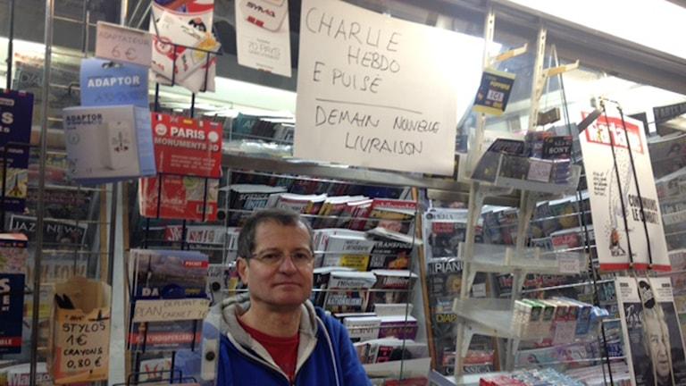 En man står i en kiosk i Paris under en skylt på franska där det står att tidningen Charlie Hebdo är slutsåld.