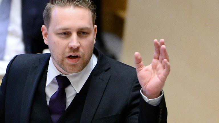 Mattias Karlsson höjer näven i Riksdagen.