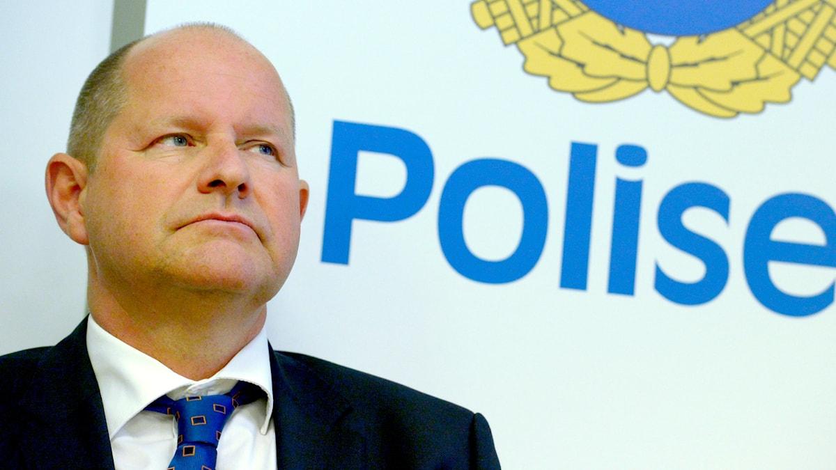 Rikspolischef Dan Eliasson mot en bakgrund av polisens vapensköld.