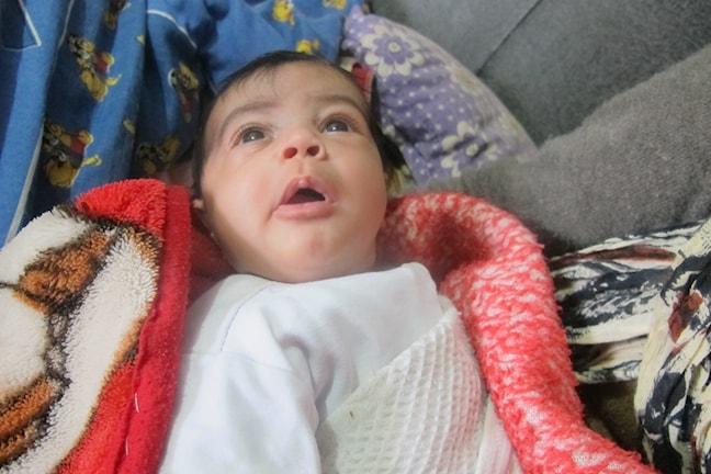Bebisen Maya ligger insvept i en filt i ett tältläger i i Bekaadalen i Libanon. Foto: Katja Magnusson/Sveriges Radio.