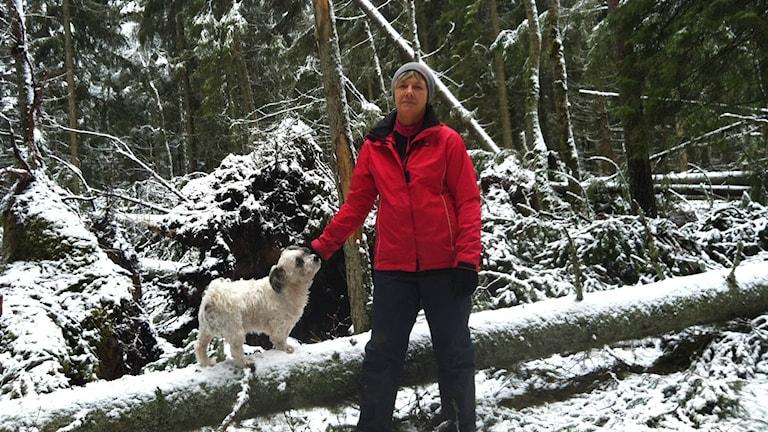 Ann Karlsson står med sin hund i sin stormskadade skog.