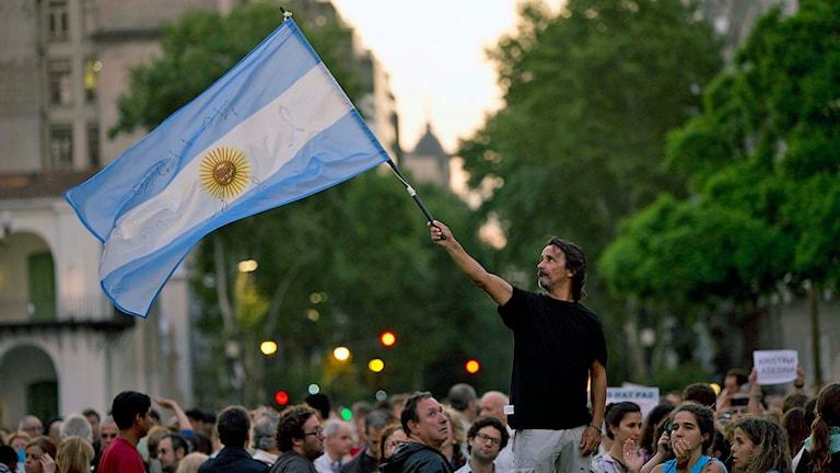 En demonstrant håller upp den argentinska flaggan på torget Plaza de Mayo efter att åklagaren Alberto Nisman hittades död i sin lägenhet. Foto: AP Photo / Rodrigo Abd / TT.