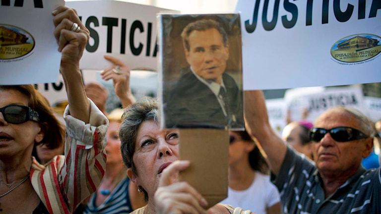 En kvinna håller upp ett foto på den döda åklagaren Alberto Nisman. Foto: AP Photo / Rodrigo Abd / TT.