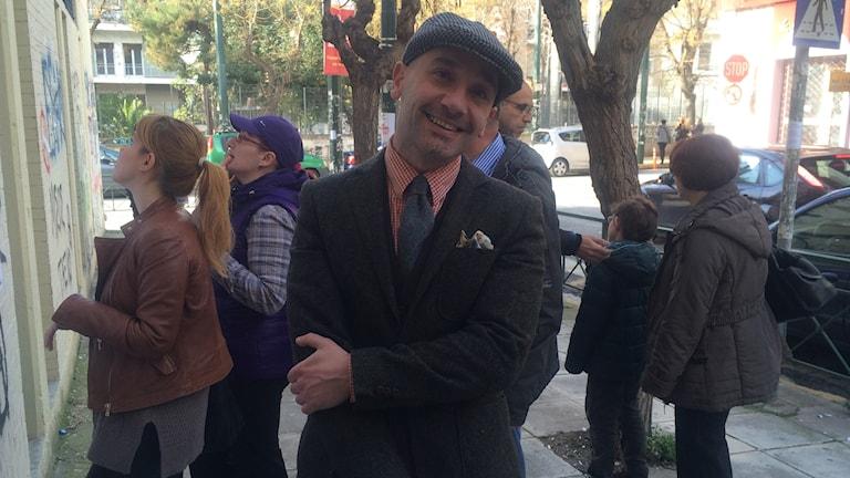 Väljaren Nikos Kourampas klädd i kavaj och slips utanför vallokal i Aten. Foto: Johanna Melén/Sveriges Radio