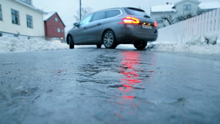 Bild står på snedden på isig väg med vatten ovanpå