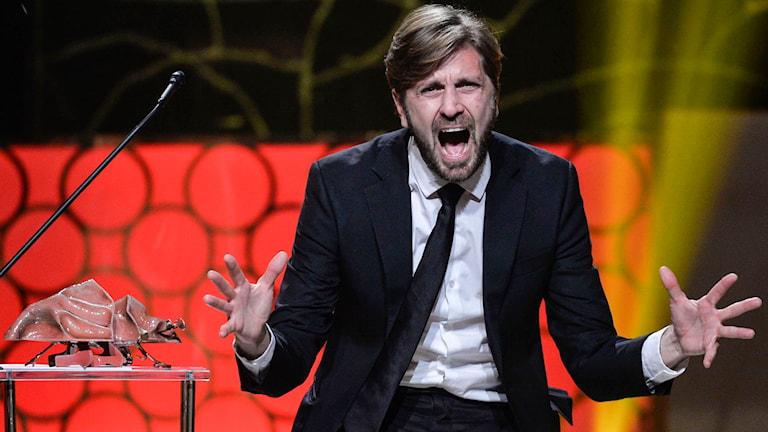 Ruben Östlund i eufori när han tar emot pris för bästa regi. Foto: TT