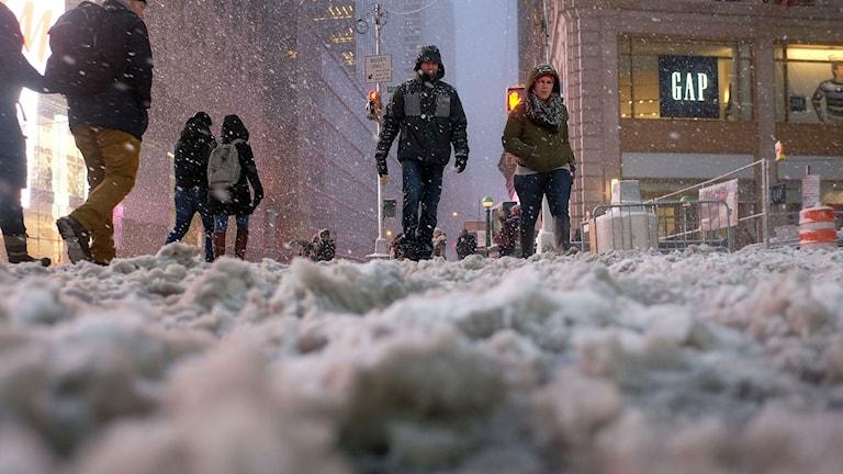 Människor skyndar fram genom en snötäckt gata vid Times Square. Foto: TT.