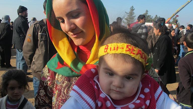 En mamma firar firar Kobanes befrielse med sitt barn i famnen. Foto: Katja Magnusson / Sveriges Radio