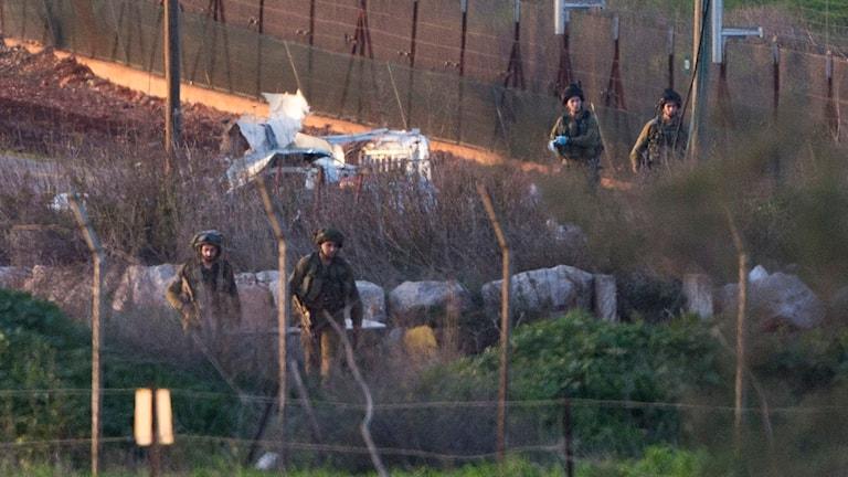 Israeliska soldater vid militärfordon som träffades av en missil från Hizbollah idag. Foto: AP