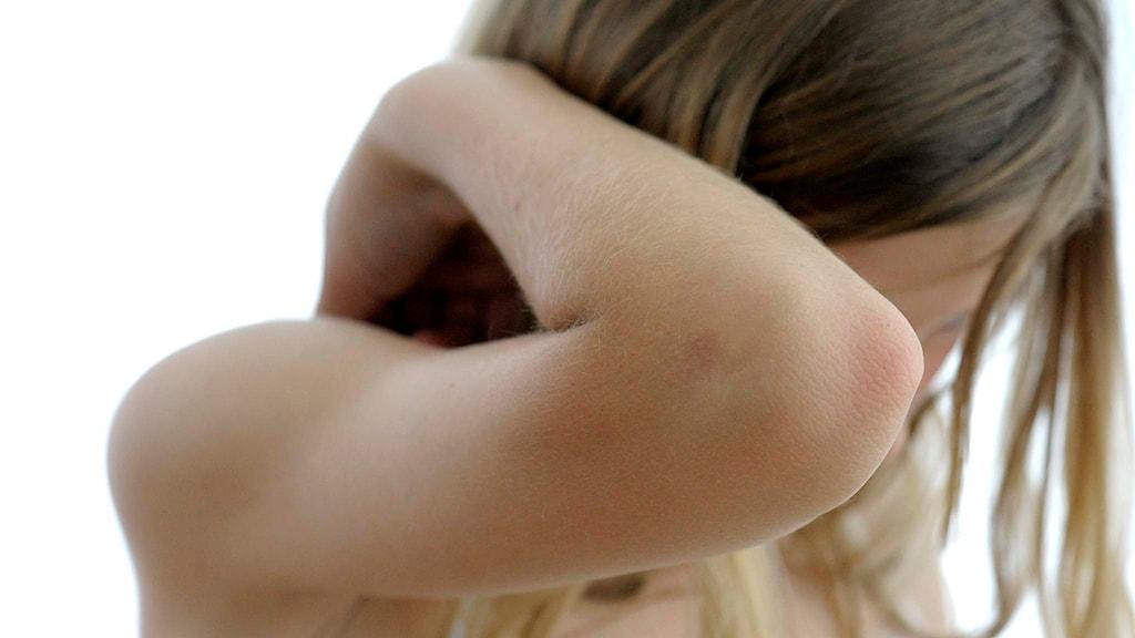 Flicka håller upp armen som skydd för ansiktet. Foto: Janerik Henriksson/TT.