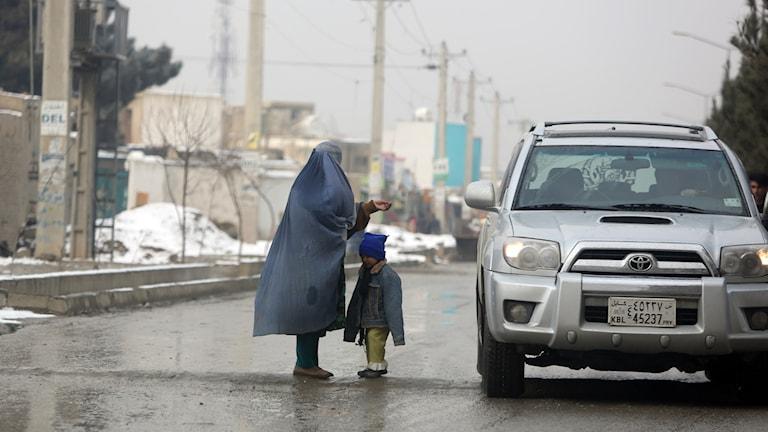 En kvinna står på en gata i huvudstaden Kabul tillsammans med ett barn och tigger. Foto: Rahmat Gul/TT.