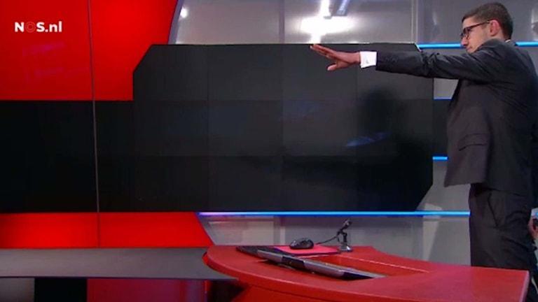 Bild tagen från nederländsk tv som visar beväpnad man som tagit sig in i tv-huset. Foto: TT.