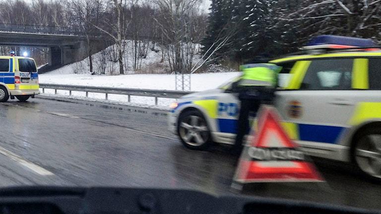 """Två polisbilar vid en olycksplats på en motorväg. En skylt med texten """"olycka"""" står på vägen. Foto: Margareta Gustafsson/TT."""