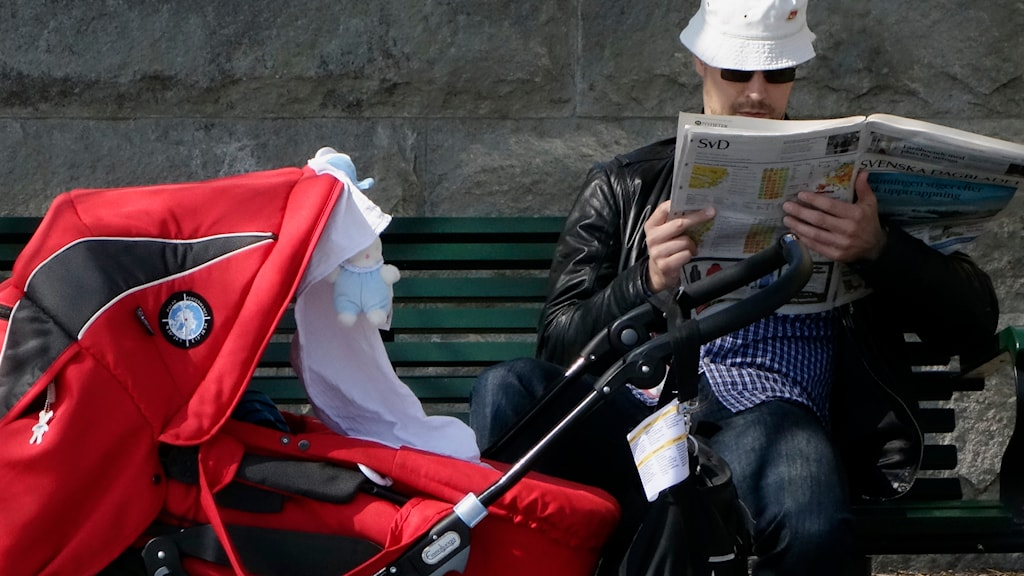 Man sitter på parkbänk och läser tidningen, framför honom en röd barnvagn. Foto: Hasse Holmberg/TT
