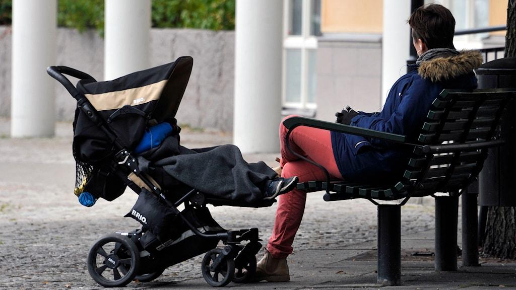 Kvinna sitter på parkbänk, barnvagn framför henne. Foto: Hasse Holmberg/TT