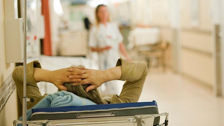 En person ligger i en säng i en korridor på Södersjukhusets akutmottanging.