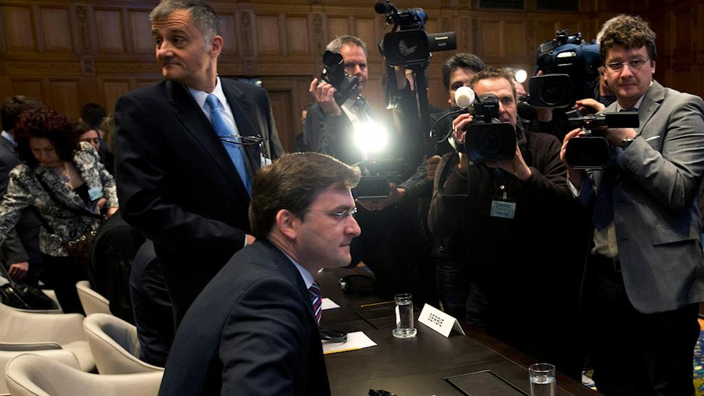 Serbiens justitieminister, Nikola Selkovic, sätter sig ner framför journalisters kameror och den internationella brottsmålsdomstolen i Haag. Foto: TT