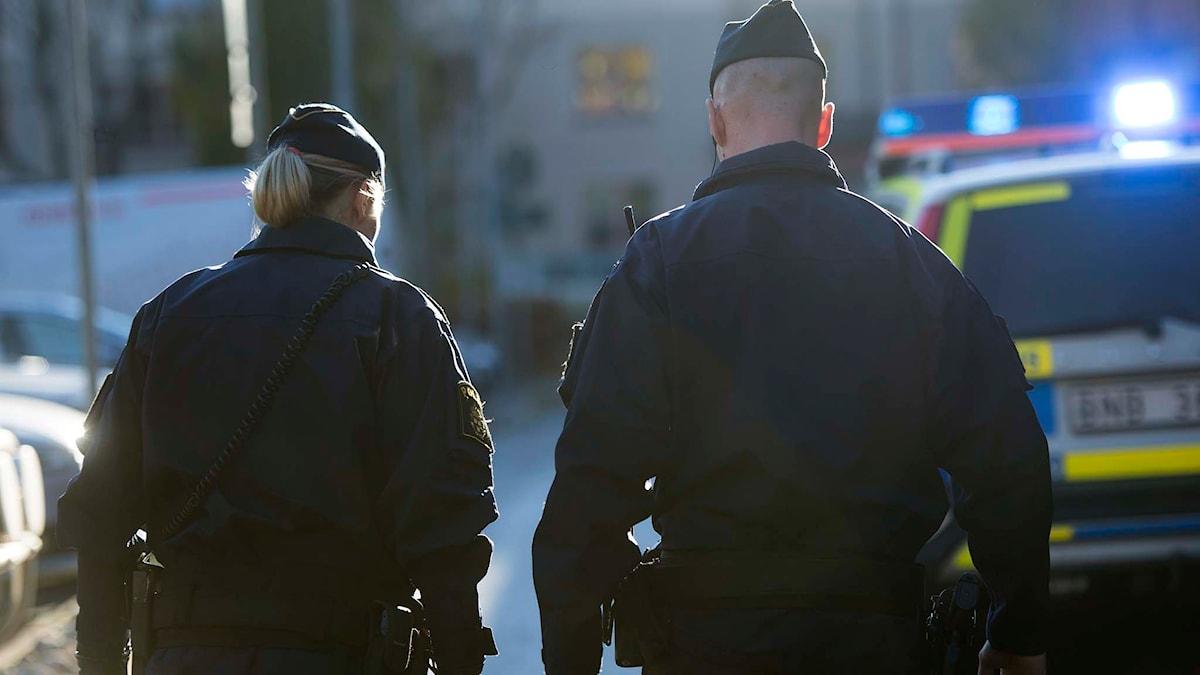 Två poliser framför en polisbil. Foto: Foto: Fredrik Sandberg/TT.