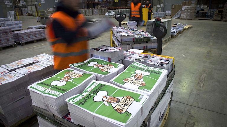 Tidningstravar innehållande den franska satirtidningen Charlie Hebdo. Foto: Martin Bureau/TT.