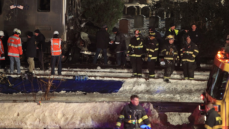 Minst sju människor dog när ett lokaltåg körde in i en bil som befann sig på spåret utanför New York på tisdagskvällen lokal tid. Räddningspersonal på olycksplatsen. Foto: TT/AP