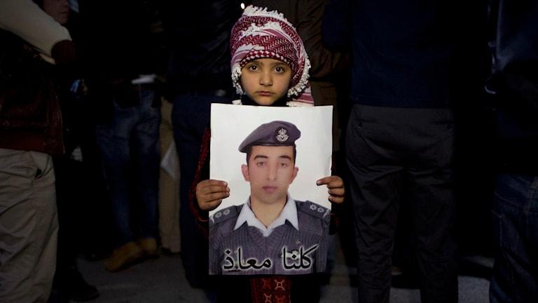 Barn håller upp bild på Muaz al-Kasasbe som mördats av terrorgruppen IS. Foto: Nasser Nasser/AP.