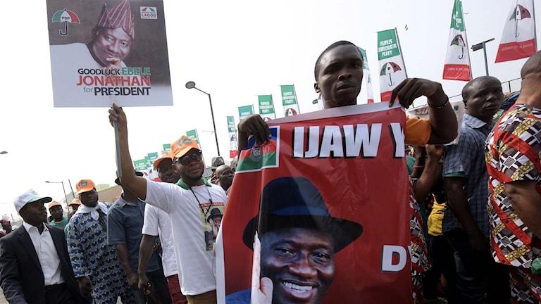 En anhängare till Nigerias president Goodluck Jonathan en valaffisch med presidentens ansikte. Foto: Pius Utomi Ekpei/TT.