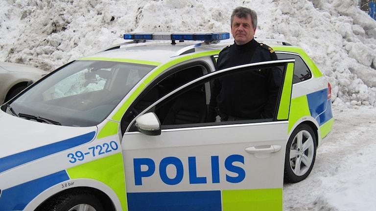 Bild på Fredrik Ståhle som står vid förarplatsen på en polisbil.