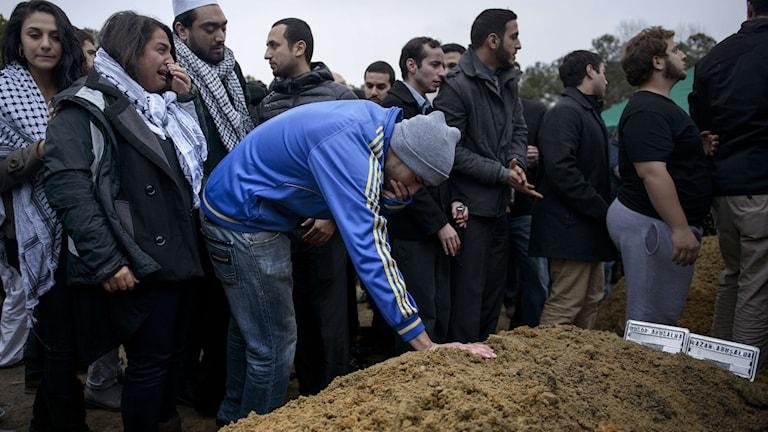 En begravning, en ung man böjer sig ned och håller handen på sanden som täcker graven.