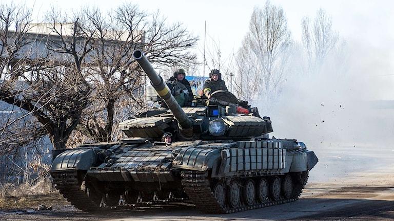 En ukrainsk pansarvagn men två soldater som sitter uppe på den.