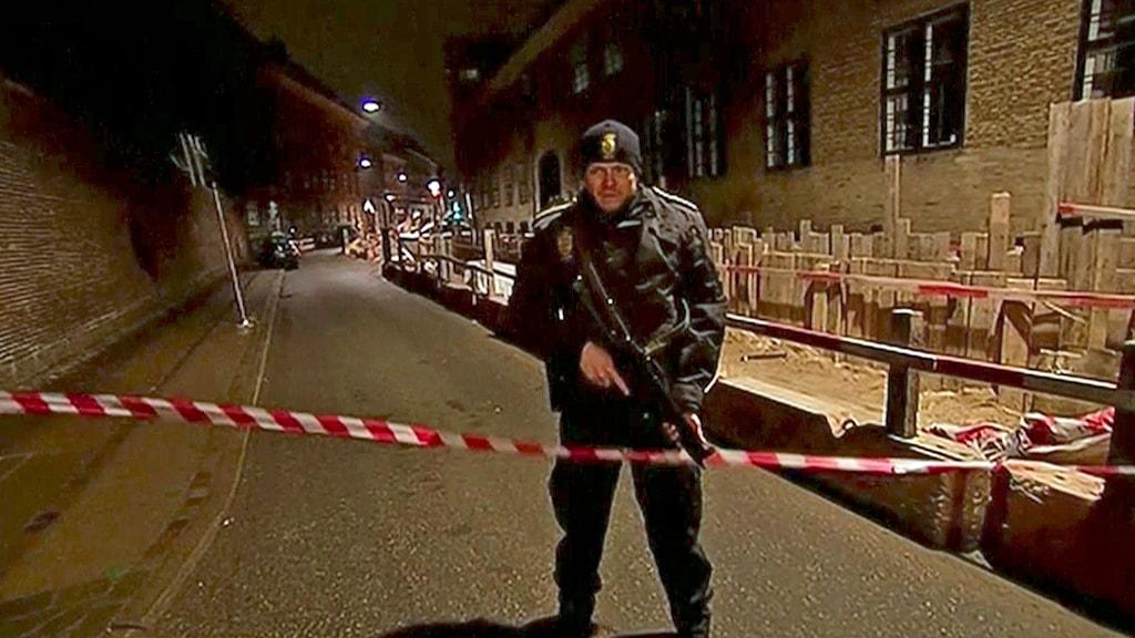 En beväpnad polis vid avspärrningarna nära Köpenhamns synagoga. Foto: AP Photo/TV2/TT.