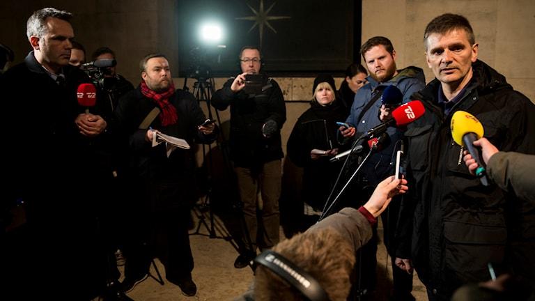 Polisensn talesman står omringad av reportrar som håller fram mikrofoner.