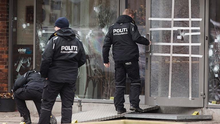 Polisens tekniker undersöker den sönderskjutna entrén till kulturhuset Krudttønden i stadsdelen Østerbro i Köpenhamn. Foto: Ola Torkelsson/TT.