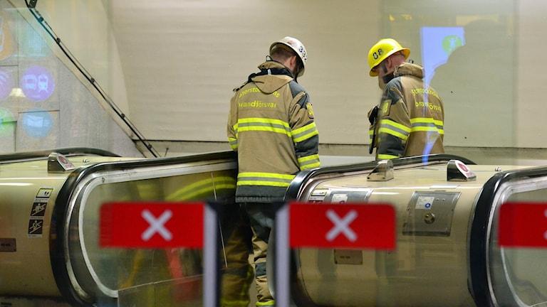 Brandmän på väg ned i rulltrappan på Östermalmstorgs tunnelbanestation för att undsätta en kvinna som fastna på lördagen. Foto: Johan Nilsson/TT.
