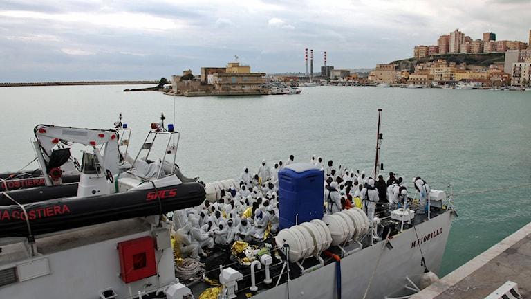 Flyktingar väntar på att få lämna ett av den italienska kustbevakningens fartyg. Foto: Francesco Malavolta/TT.