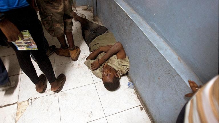 En man väntar på att få läkarvård på sjukhuset i Port-au-Prince. Foto: AP Photo / Dieu Nailo Chery.