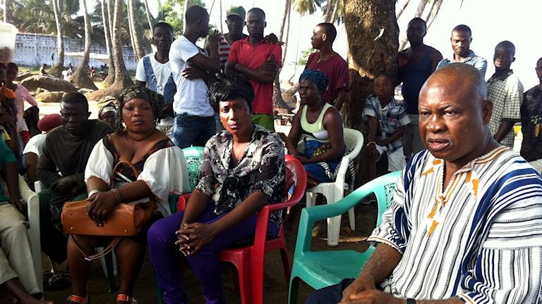 Theresa Bayou på fiskeorganisationen LAFA i Liberia lyssnar på bitr. jordbruksminister Dr. Sizi Suba i fiskebyn King gray. Foto: Johan Bergendorff / Sveriges Radio