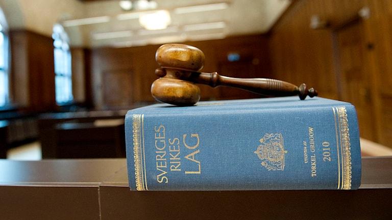 En domarklubba ligger på en lagbok i en tingsrättssal. Foto: Jessica Gow/TT.