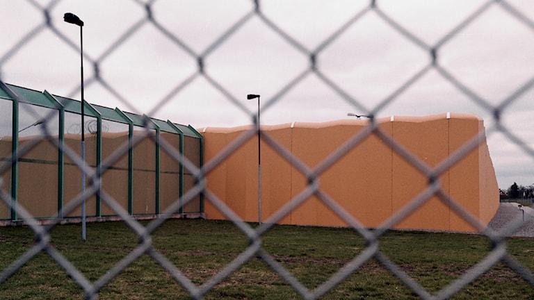 Stängsel i förgrunden och i bakgrunden en mur på Kumlaanstalten.