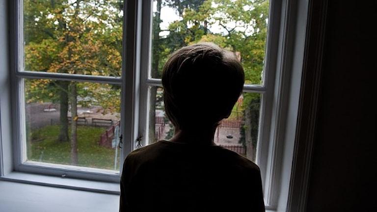 Ett barn tittar ut genom ett fönster. Foto: TT
