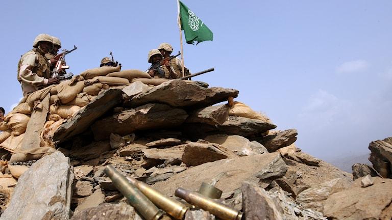 Soldater på en höjd med Saudiarabiens flagga i bakgrunden och en hög med tomhylsor i förgrunden. Foto: Hassan Ammar/TT.