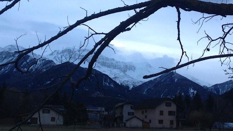 Några hus i förgrunden, i bakgrunden alper.