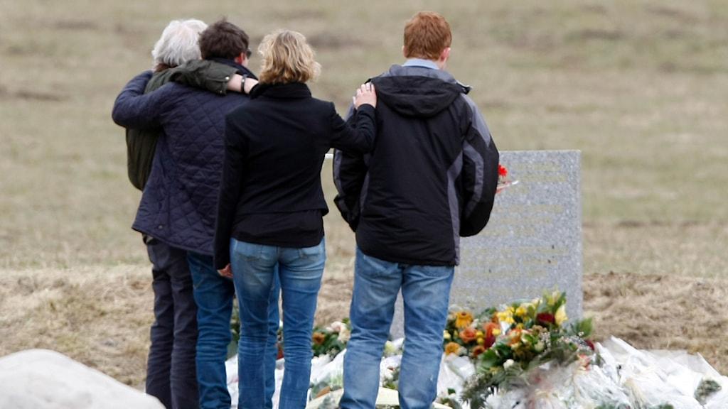 Anhöriga vid en minnessten som satts upp i området där planet kraschade. Foto: Claude Paris/TT.