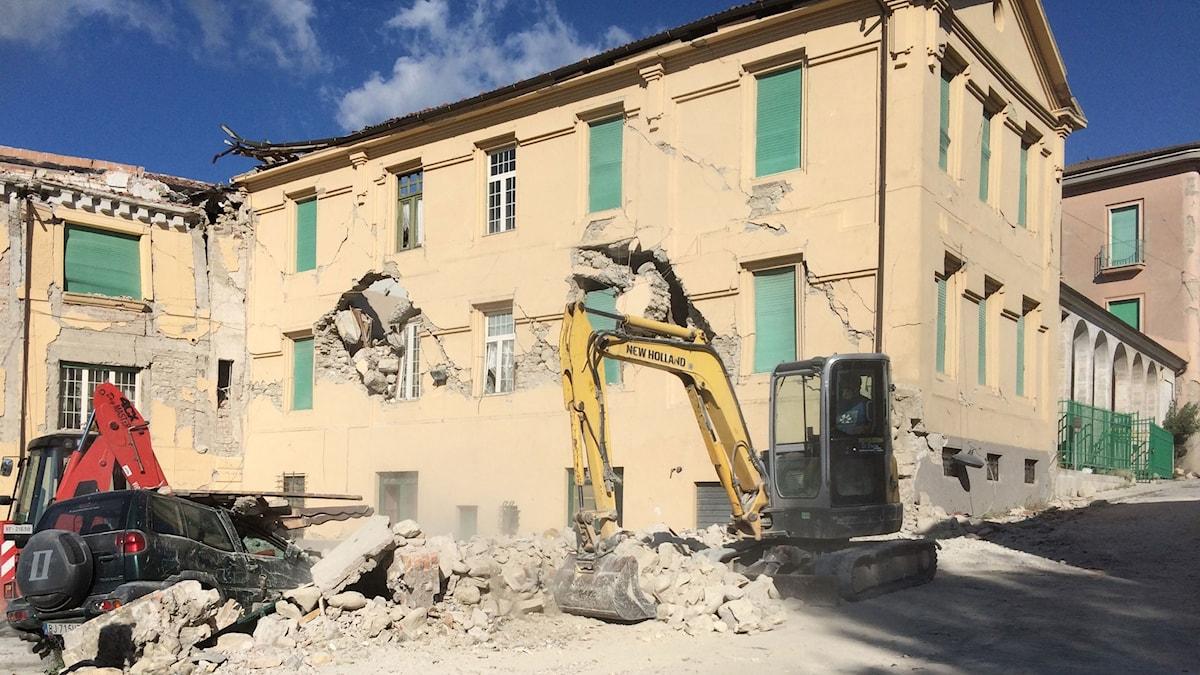 grävskopa framför raserat hus
